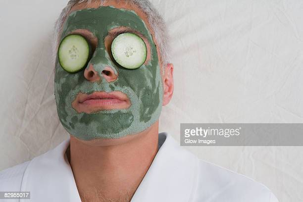 Close-up of a mature man lying on a massage table with facial mask on his face