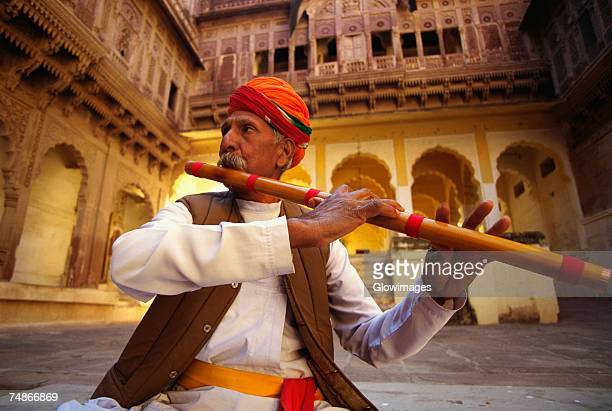 close-up of a mature man playing a flute in a fort, meherangarh fort, jodhpur, rajasthan, india - arts culture and entertainment stock pictures, royalty-free photos & images