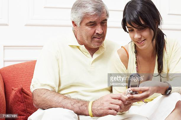 Close-up of a mature man sitting with his daughter on a couch and looking at a mobile phone