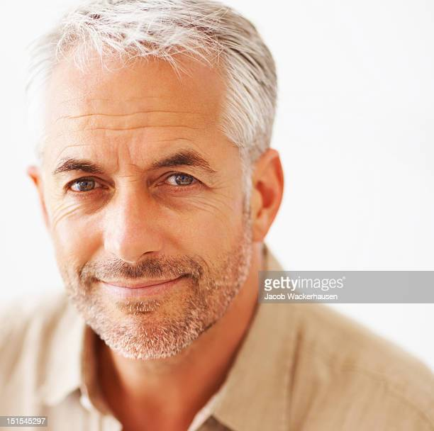 close-up of a mature man smirking - grey hair stock pictures, royalty-free photos & images