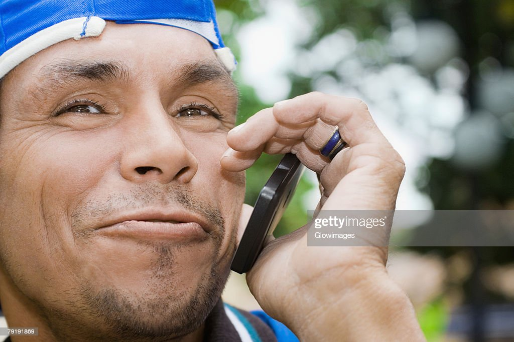 Close-up of a mature man using a mobile phone and smirking : Stock Photo