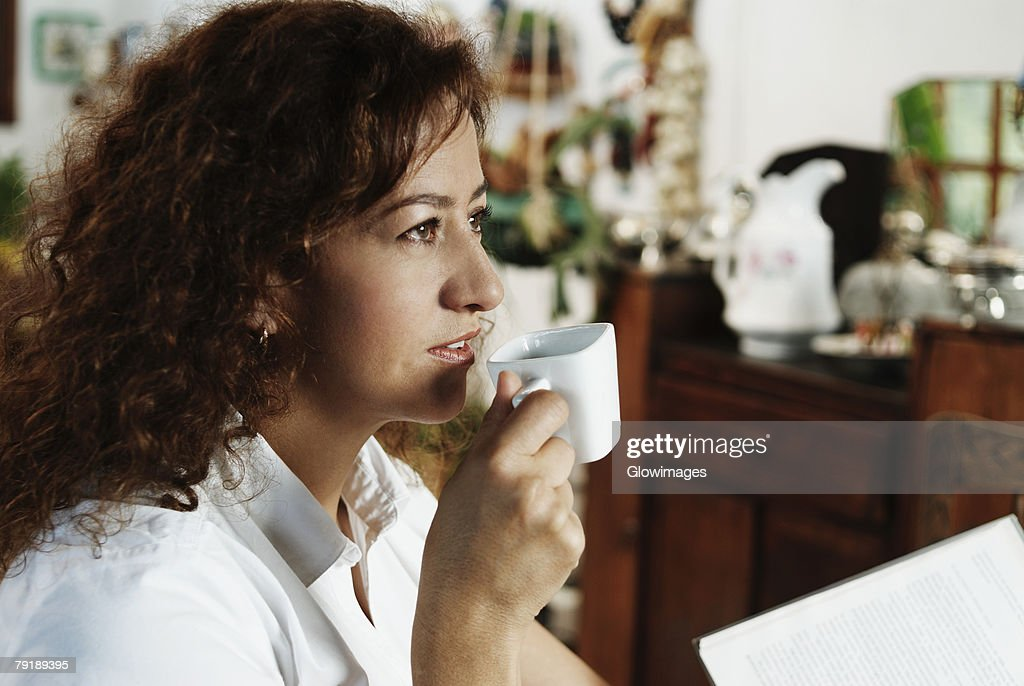 Close-up of a mature woman drinking a cup of tea : Foto de stock