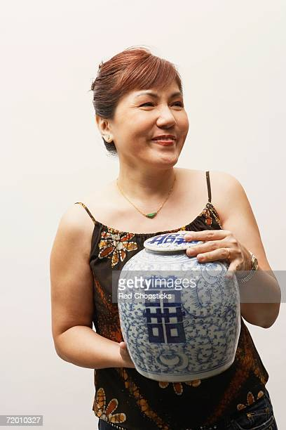 close-up of a mature woman holding an urn - urn stock pictures, royalty-free photos & images