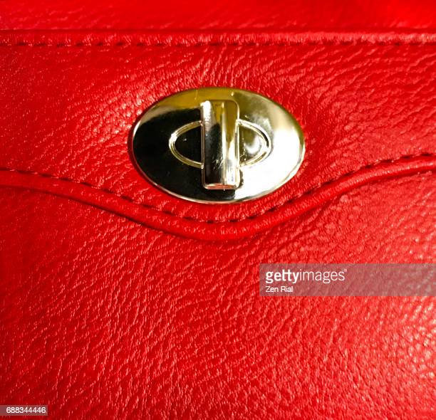close-up of a metal lock on a red-colored ladies purse - zen rial stock photos and pictures