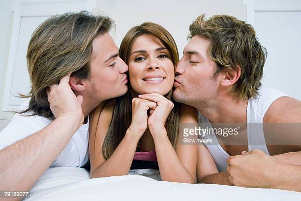 close-up of a mid adult man and a young man kissing a young woman - three people fotografías e imágenes de stock