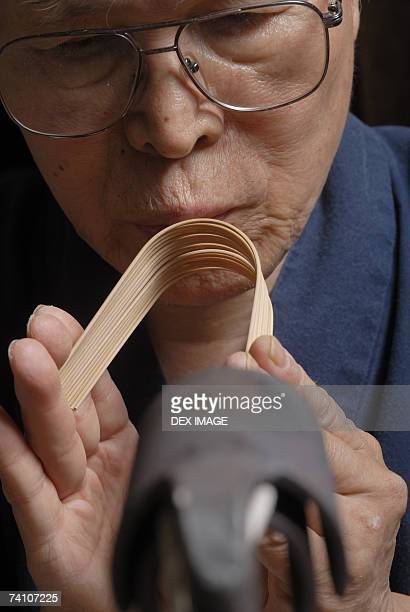 close-up of a mid adult man bending a bamboo strip - bamboo instrument stock photos and pictures