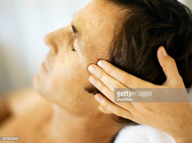 close-up of a mid adult man having a head massage - head massage stock photos and pictures