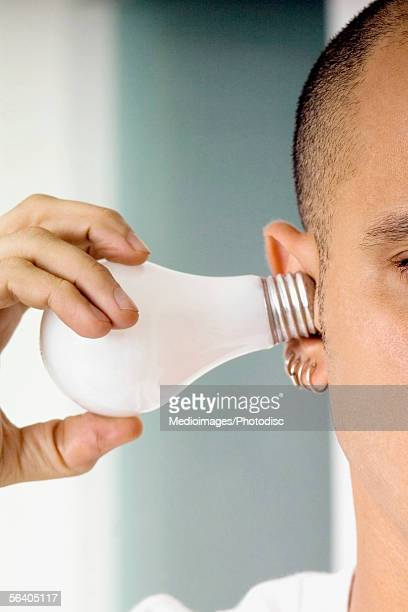 Close-up of a mid adult man holding a light bulb in his ear