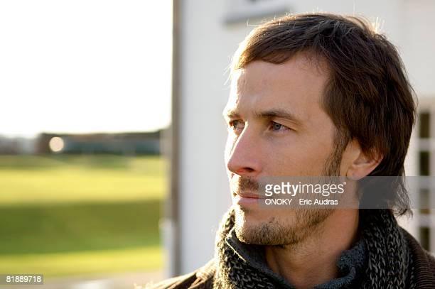 close-up of a mid adult man looking away - onoky stock-fotos und bilder