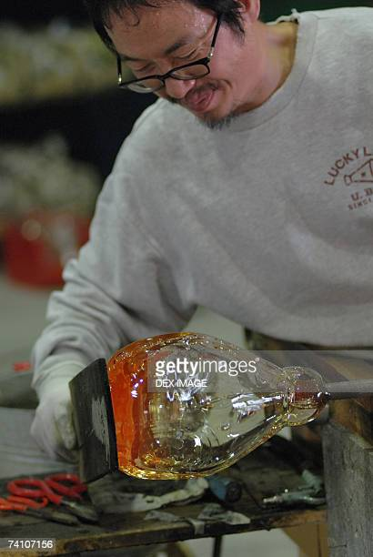 Close-up of a mid adult man molding a glass bulb