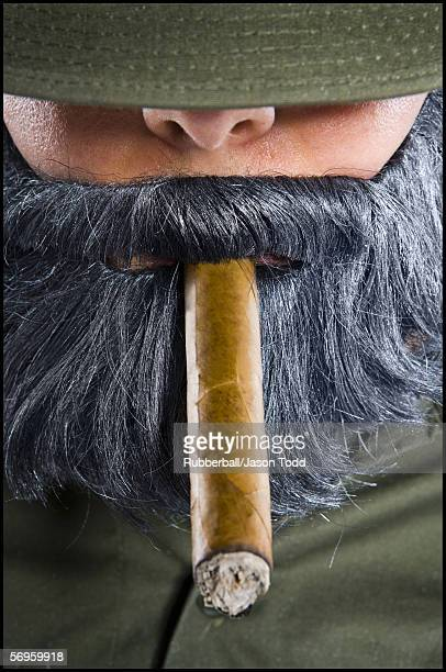 close-up of a mid adult man smoking a cigar - uniform cap stock pictures, royalty-free photos & images
