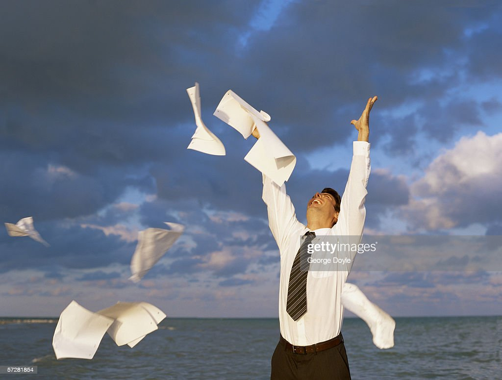 Close-up of a mid adult man throwing away papers : Stock Photo