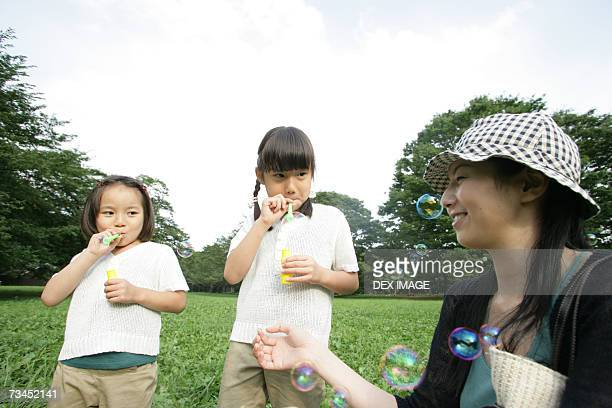 Close-up of a mid adult woman and her two daughters blowing bubbles in the park