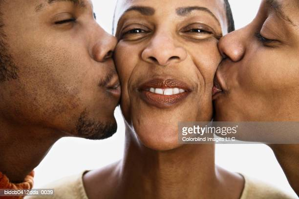 Close-up of a mid adult woman being kissed by a young man and a young woman