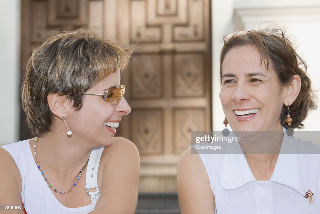 Close-up of a mid adult woman sitting with a mature woman and laughing : Foto de stock