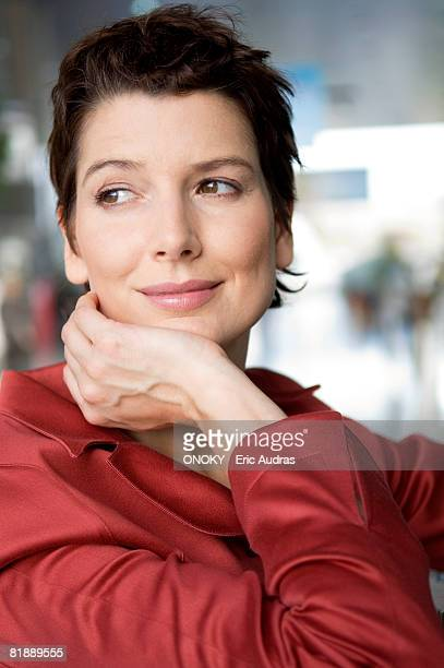 close-up of a mid adult woman smiling with her hand on her chin - onoky stock-fotos und bilder