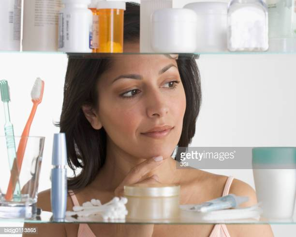 close-up of a mid adult woman standing in front of a bathroom cabinet - medicine cabinet stock pictures, royalty-free photos & images