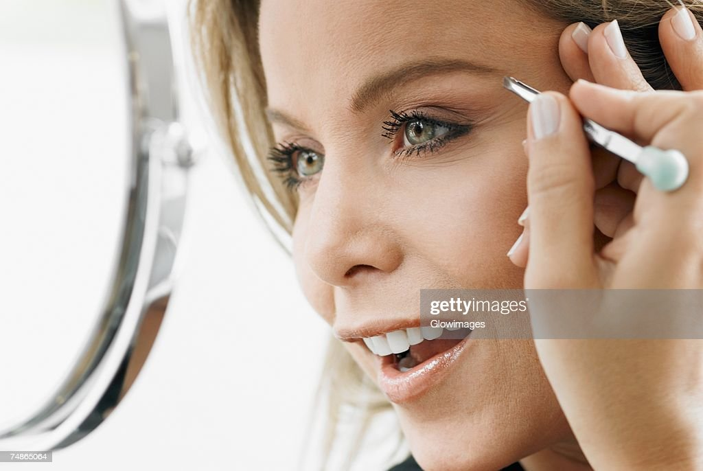 Close-up of a mid adult woman tweezing her eyebrows : Stock Photo