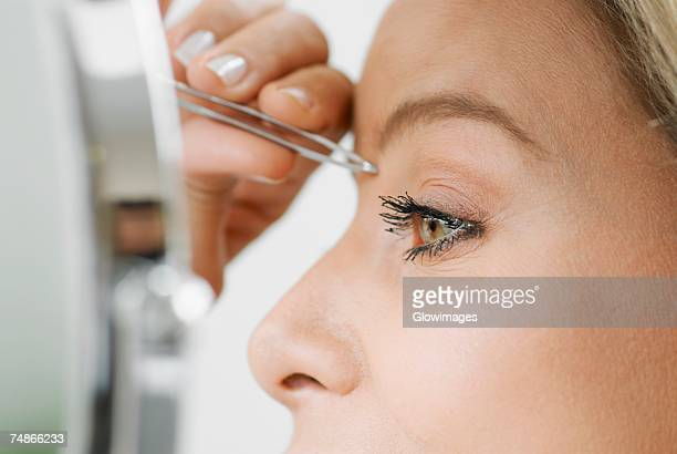 Close-up of a mid adult woman tweezing her eyebrows