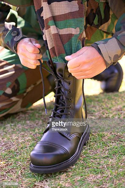 Close-up of a military soldier tightening and tying the left boot.