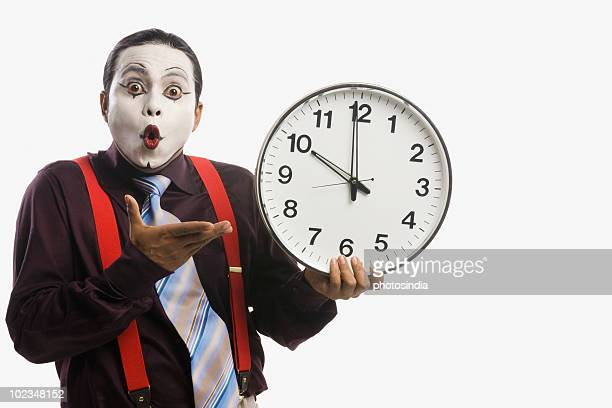 Close-up of a mime showing a clock