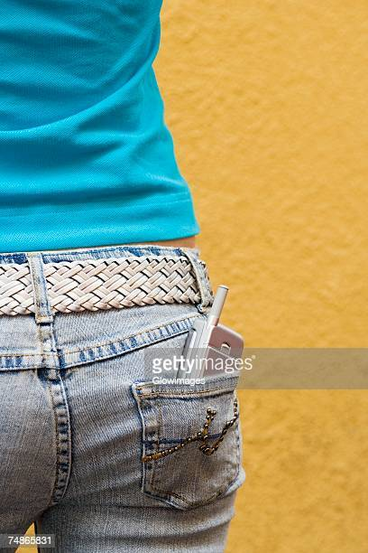 Close-up of a mobile phone in a teenage girl's back pocket