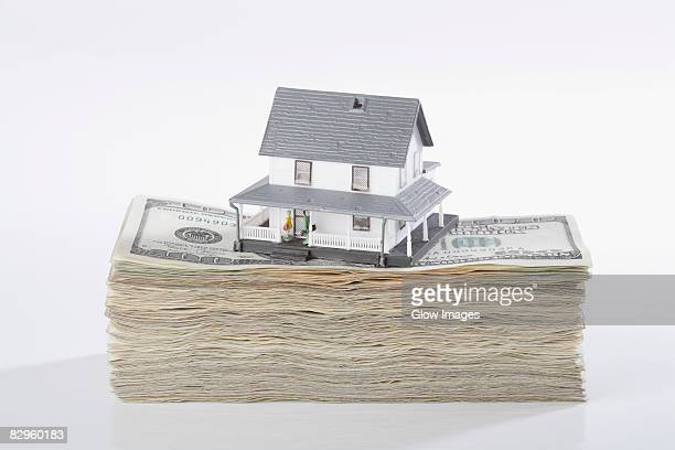 Close-up of a model home on the top of US dollar bills