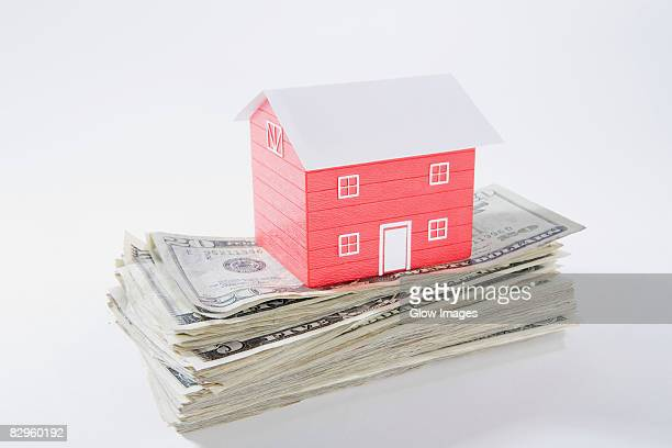 Close-up of a model home on the top of US paper currency