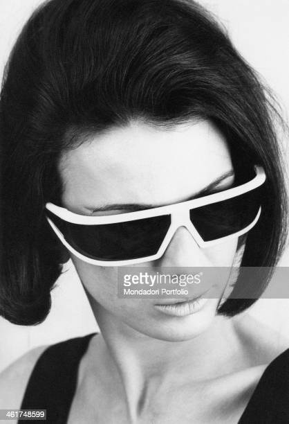 Closeup of a model who shows off big black flashy sunglasses with a thick white frame advertising a new line with an aggressive design for women in...