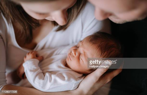 a close-up of a mother and father holding a newborn baby son at home. - twee ouders stockfoto's en -beelden