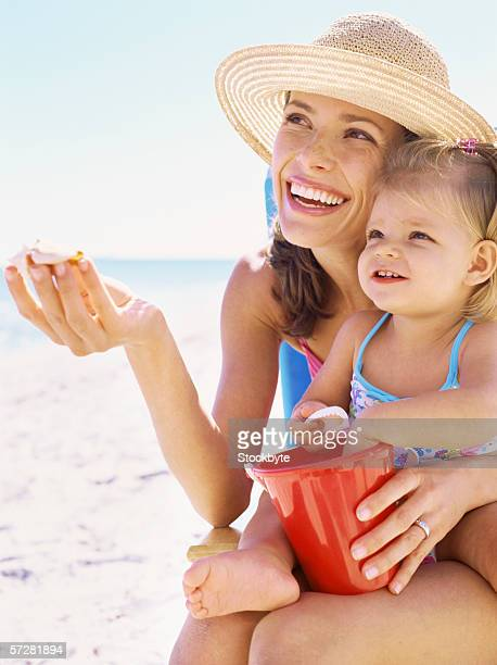 Close-up of a mother on the beach holding her daughter