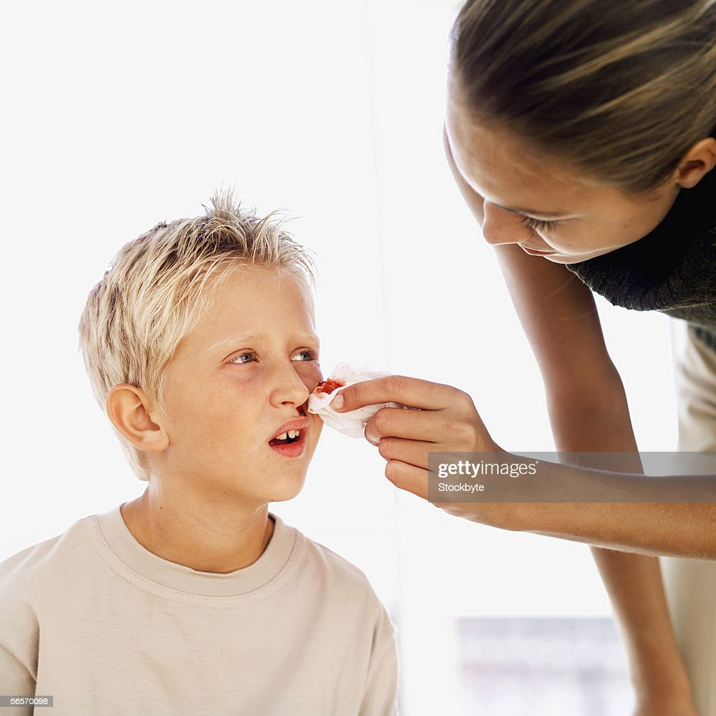 close-up of a mother wiping her son's nose bleed : Stock Photo