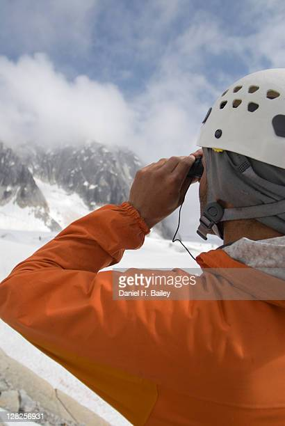 Closeup of a mountain climber looking through binoculars