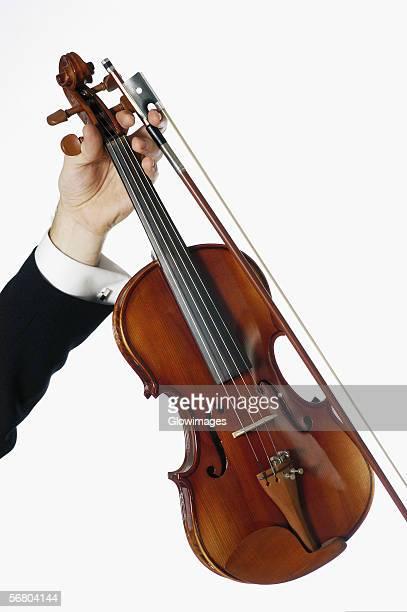 close-up of a musician's hand holding a violin - violin fotografías e imágenes de stock