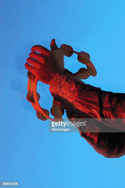Close-up of a musician's hands playing the tambourine