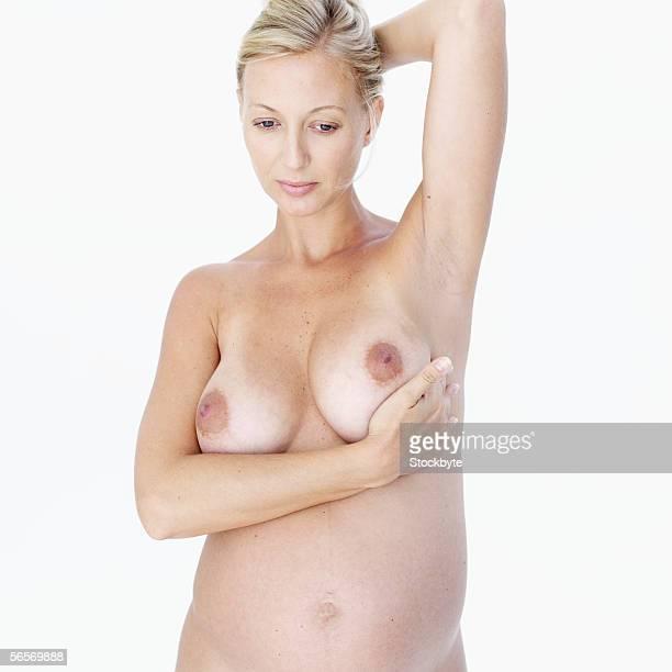 close-up of a naked mid adult pregnant woman examining her breast - weibliche brust schwanger stock-fotos und bilder