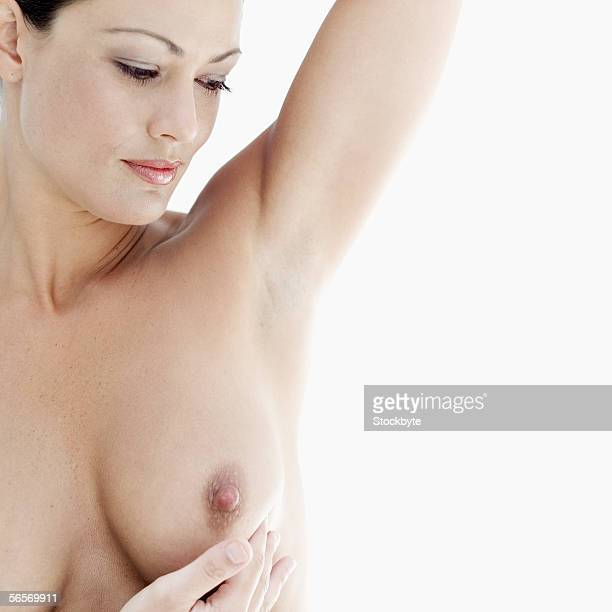 close-up of a naked young woman examining her breast - nackte frau brüste stock-fotos und bilder