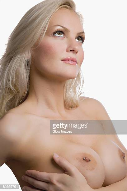 Close-up of a naked young woman touching her breast