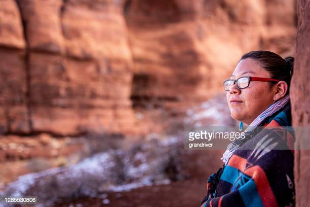 a closeup of a native american, navajo young woman wrapped up in a traditional navajo wool blanket and sitting in the iconic teardrop arch, monument valley, utah, arizona - apache stock pictures, royalty-free photos & images
