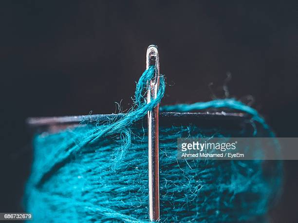 close-up of a needel and yarn reel against black background - sewing needle stock pictures, royalty-free photos & images