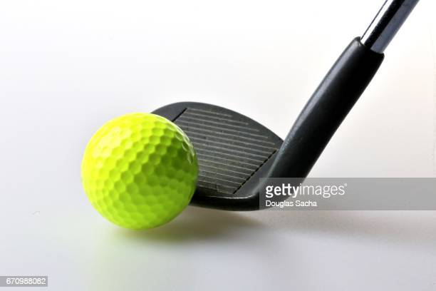 Close-up of a neon golf ball and iron golf club
