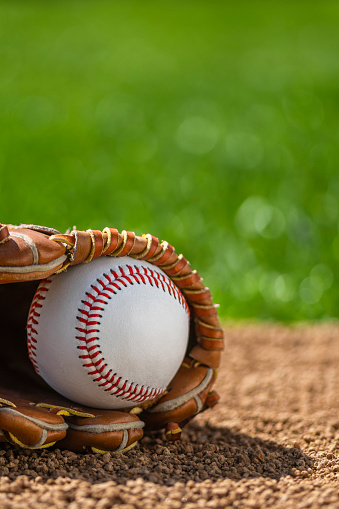 A close-up of a new baseball in a sports glove sitting in the dirt 951173274