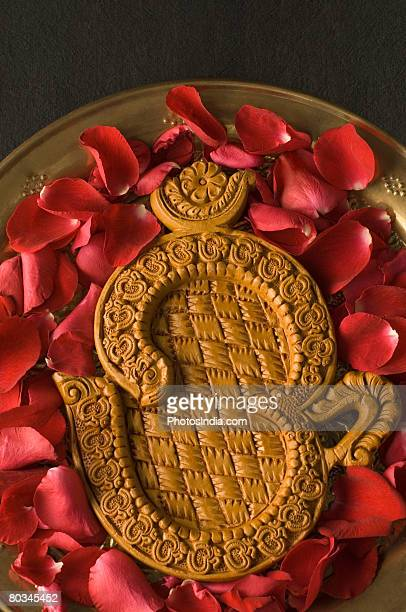 Close-up of a ohm symbol with rose petals in a plate