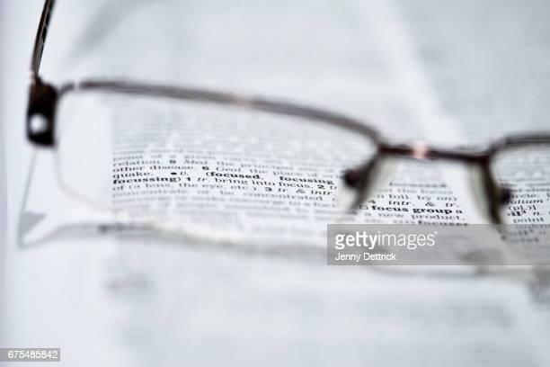 close-up of a pair of glasses on a dictionary - dictionary stock pictures, royalty-free photos & images