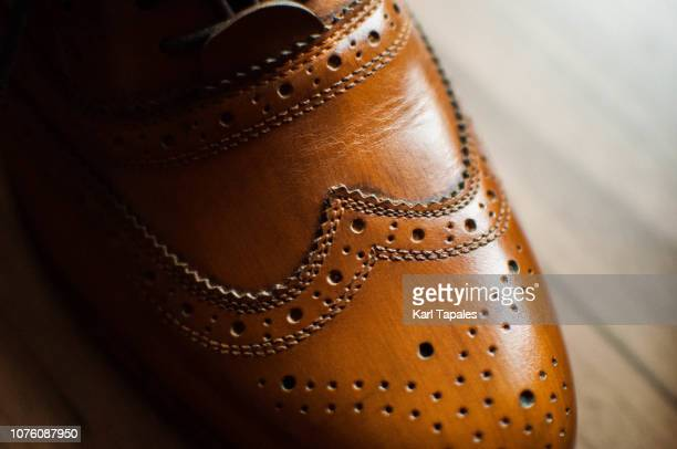 a close-up of a pair of men's shoes - brown shoe stock photos and pictures