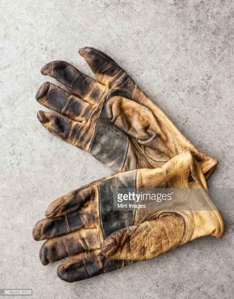 close-up of a pair of used work gloves in a shop - leather glove stock pictures, royalty-free photos & images
