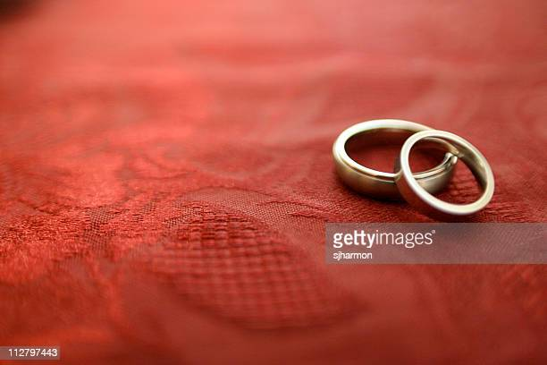 Close-up of a pair of wedding bands on red linen