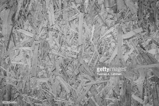 Close-up of a particle board background texture with vignetting in black and white.