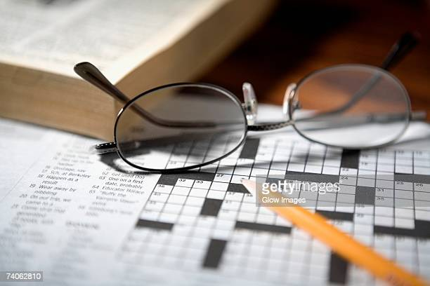Close-up of a pencil and a pair of eyeglasses on a crossword puzzle