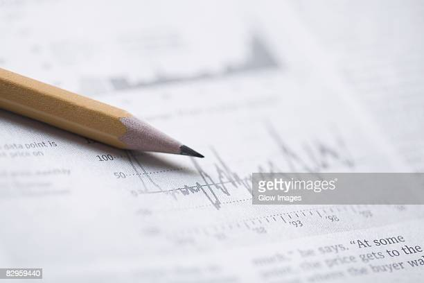 Close-up of a pencil on a financial newspaper